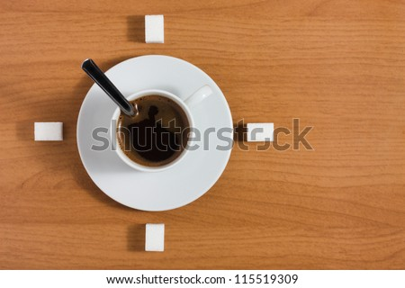 White coffee cup with saucer and sugar like a clock on a wooden brown table, top view - stock photo