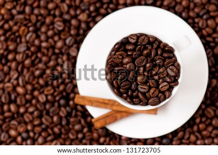 White coffee cup with spices on coffee beans - top view - focus on cup