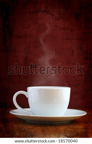 White coffee cup with steaming hot drink on grungy background - stock photo