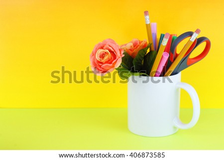 White coffee mug filled with markers, pencils, scissors and a silk rose on a green and yellow background good for secretary's day, or administrative professionals day - stock photo