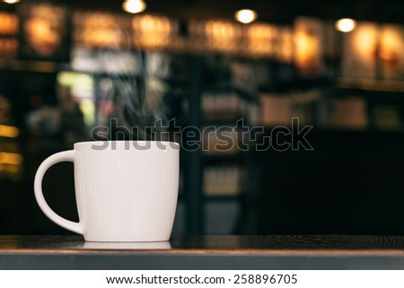White Coffee Mug On Wooden Table In Cafe With Copyspace : Smoke Filtered - stock photo