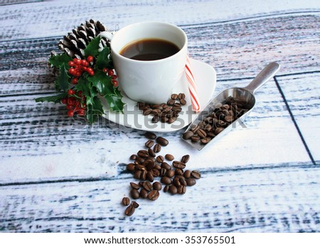 white coffee mug with coffee candy cane holy leaf and pine cone with coffee beans spilling out of a metal shovel on a wooden background/candy cane coffee/holy sweet energy - stock photo