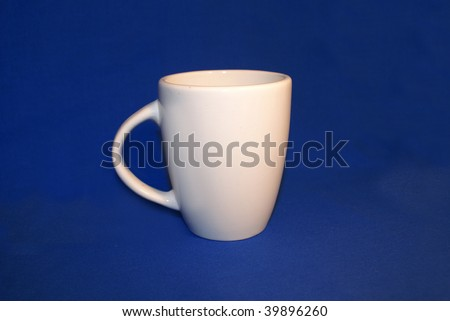 White coffee/tea mug, isolated on blue . Room for logo.