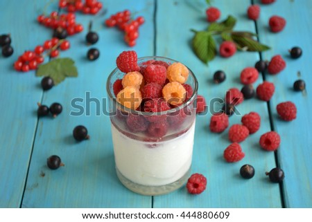 White cold yogurt with fresh summer berries - red and yellow raspberry, red  and black currants. Healthy breakfast. Tasty dessert is on a blue wooden background.  Fitness food. - stock photo