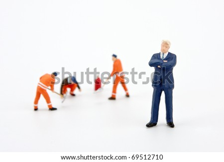 White collar businessman and workers on computer hard drive - stock photo