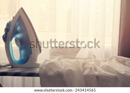 white collar shirt and iron on ironing board - stock photo