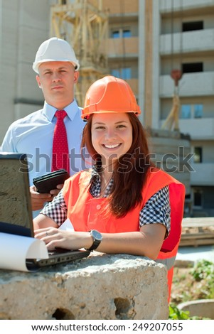 White-collar workers wearing protective helmet works on the building site - stock photo