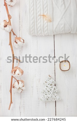White collection of winter or Christmas decorations - knitted sweater, candle, fur tree and cotton branch, on wooden table - stock photo