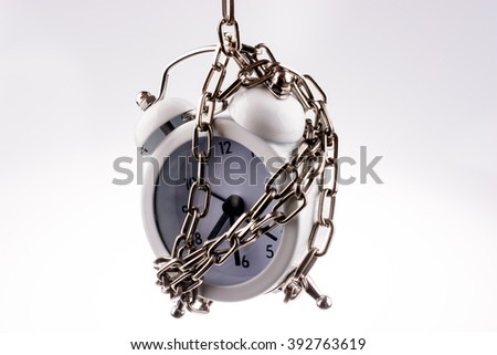 White color alarm clock in chain on a white background