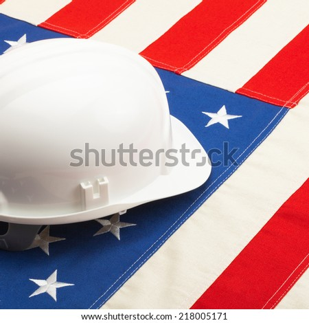 White color construction helmet laying over US flag - closeup shoot - 1 to 1 ratio
