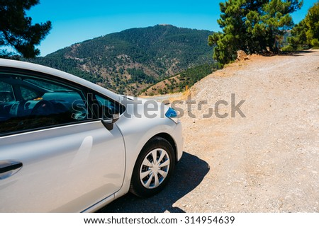 White color small hatchback car on Spainish nature landscape background.