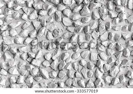 White colored wall with pebbles as background. - stock photo