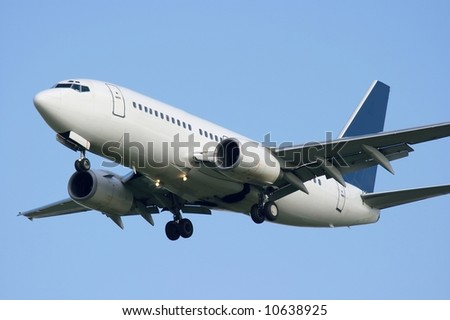 White commercial airplane against clear blue sky - stock photo