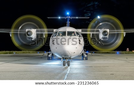 White commercial plane with engines running and propeller blur on a night with the moon on background - stock photo