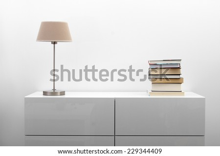 white commode with lamp and books in bright minimalism interior - stock photo