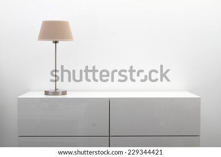 white commode with table lamp in bright minimalism interior - stock photo