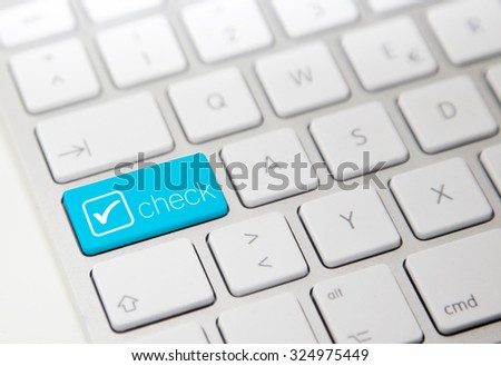 White computer keyboard with check button - stock photo