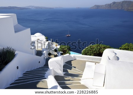 White concrete staircases leading down to the beautiful bay with clear blue sky and sea at Santorini, Greece