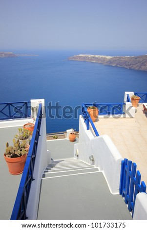 White concrete staircases leading down to the beautiful bay with clear blue sky and sea at Oia Santorini, Greece