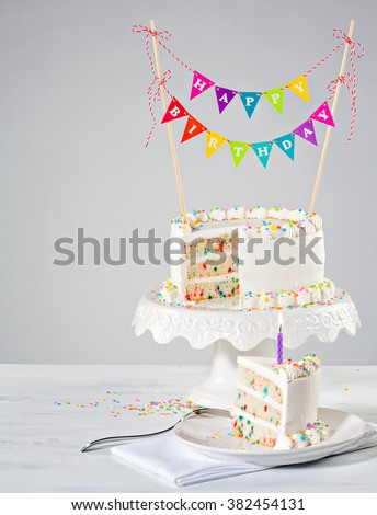 White Confetti Birthday Cake with Sprinkles and Colourful Bunting - stock photo