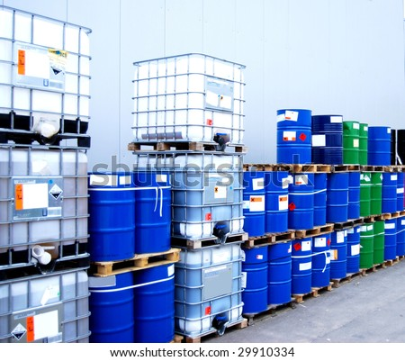 White container and blue drums on an industrial storage site - stock photo