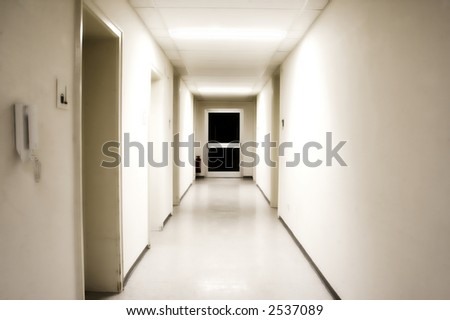 White corridor with black door at the end - stock photo