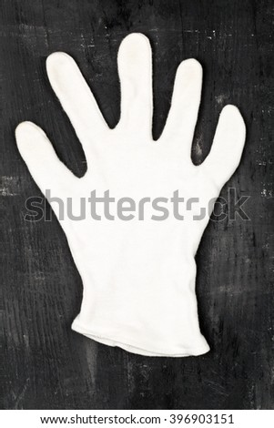 White cotton glove on black grunge painted wooden board - stock photo
