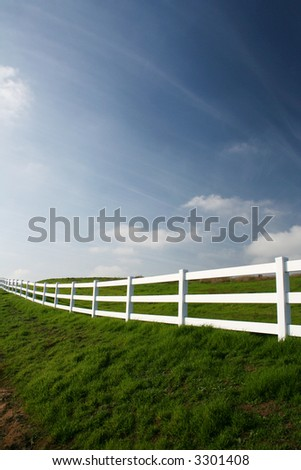white country fence in green pasture in spring - stock photo