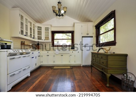 White country style kitchen with open white wooden peak roof, vintage oven cherry wooden hardwood floor, framed windows and dark olive green chest. - stock photo