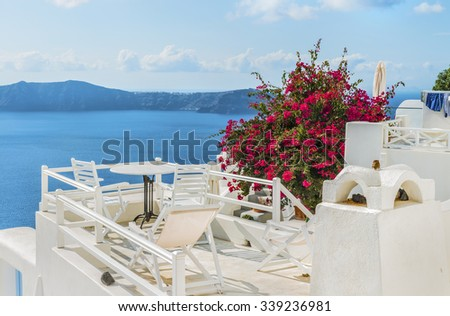 White cozy terrace with red flowers( on a plant )above the Mediterranean sea, with beautiful view of the Caldera and Therasia.Scenic natural landscape.Santorini (Thira) island.Cyclades.Greece.Europe.  - stock photo