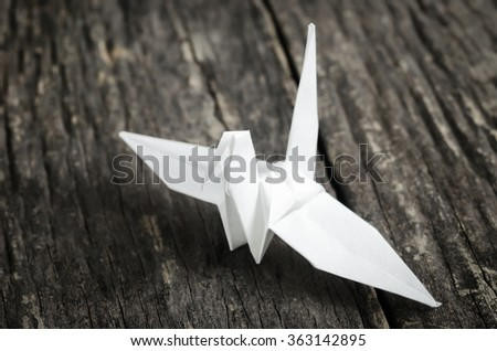 White Crane bird paper on old wooden table with vintage and vignette tone - Symbol of Peace