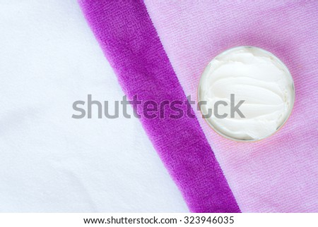 white cream  in a bowl on pink textured towel background - studio shot