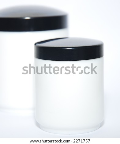 White cream jars, unlabeled, isolated on white background. Black caps. Free space for text. - stock photo