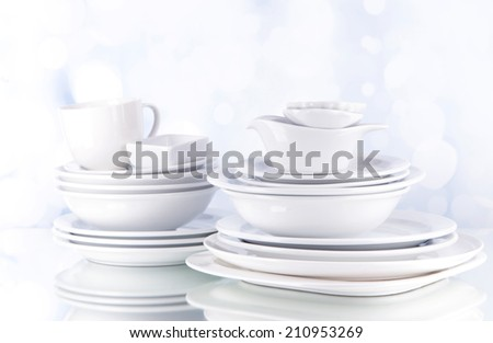 White crockery and kitchen utensils, on light background - stock photo