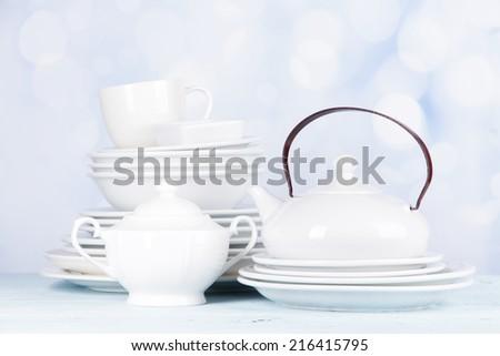 White crockery and kitchen utensils, on light background - stock photo