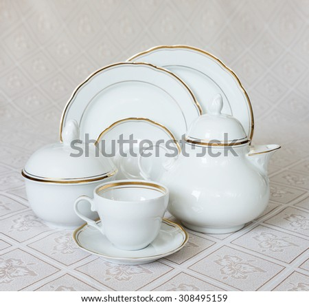 White crockery for tea: teapot, cup, serving plate and sugar bowl on a beautiful tablecloths