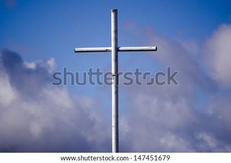 White cross against cloudy blue sky. Concept photo of christian, Christianity, religious, religion, lifestyle, belief and faith