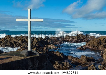 White cross by a rocky coastline with roaring waves too. - stock photo