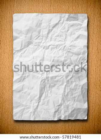 white crumpled paper on beech wood background