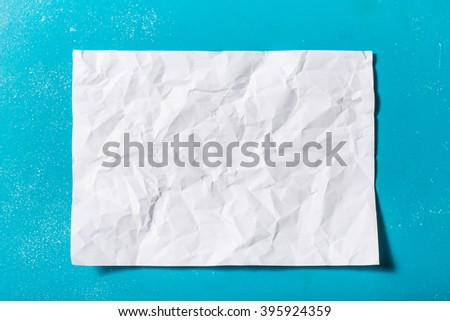 white crumpled paper on blue background