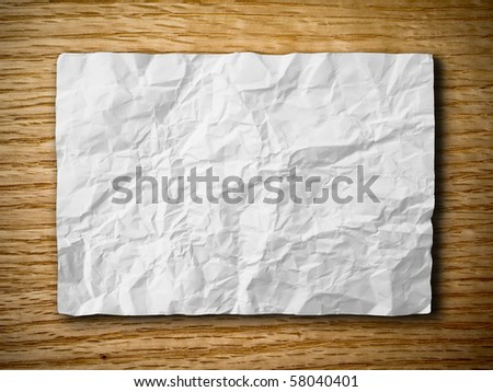 White crumpled paper on red oak wood background