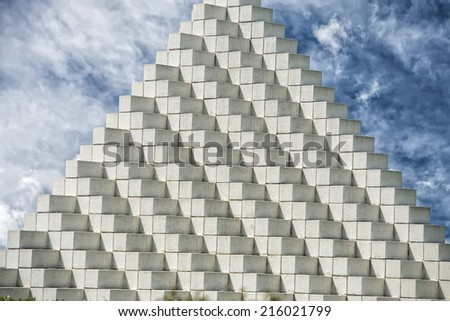 white cube pyramid on cloudy sky background - stock photo