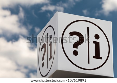 White cube shaped notice sign with question and exclamation marks against a blue cloudy sky - stock photo