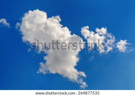 White cumulus clouds against a bright blue sky on a sunny day. - stock photo