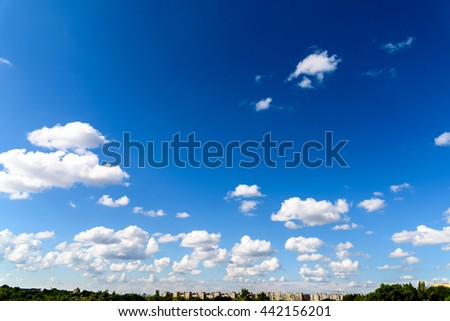 White Cumulus Clouds On Blue Sky Above Bucharest City Buildings In Romania - stock photo