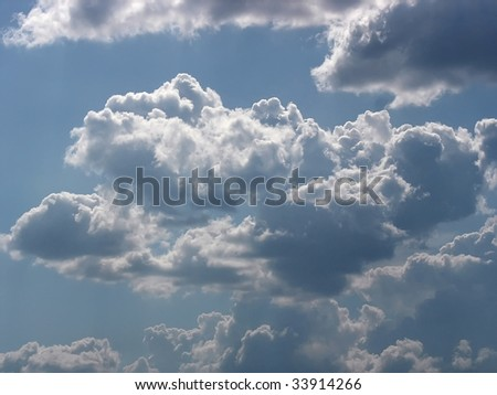 white cumulus clouds over blue sky background