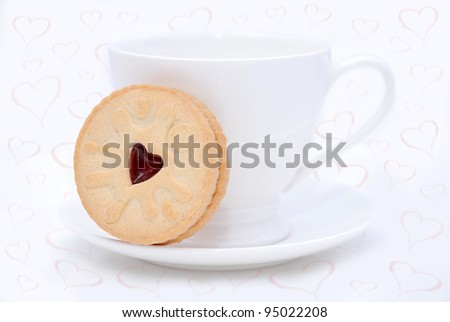 White cup and cookie on the saucer on the white background with pink hearts