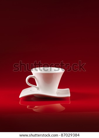 white cup and saucer of coffee, on red background - stock photo