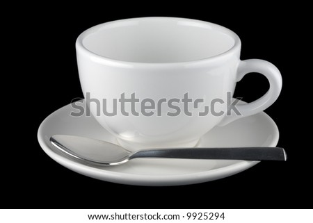 White cup and saucer with spoon, isolated against black background - stock photo