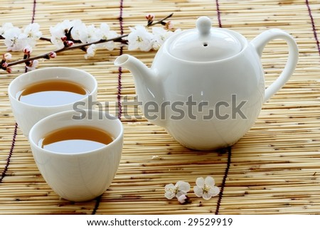 White cup and teapot on bamboo straws - stock photo